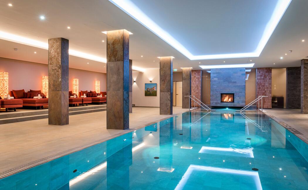 Indoor-Pool mit knisterndem Kaminfeuer
