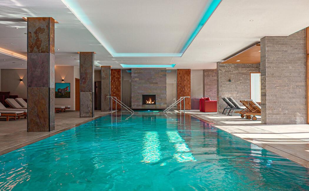 Indoor-Pool mit Kaminlounge im Panoramahallenbad des Wellnesshotel Klosterhof im Berchtesgadener Land.