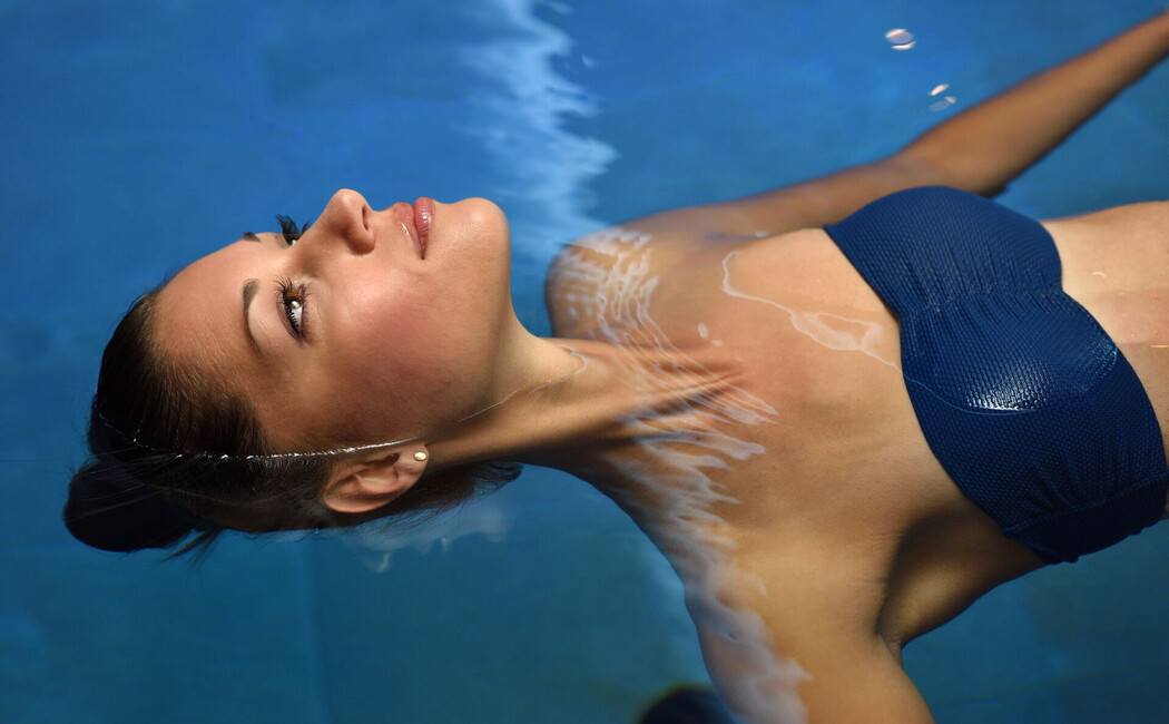 Junge Dame beim Schweben im Wasser des Solebades im Hotel Klosterhof in Bayern